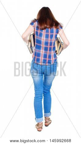 Girl comes with stack of books. back side view. Girl in plaid shirt holding out underarm textbooks.