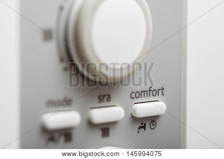The comfort setup button on control panel of DHW or central heating.