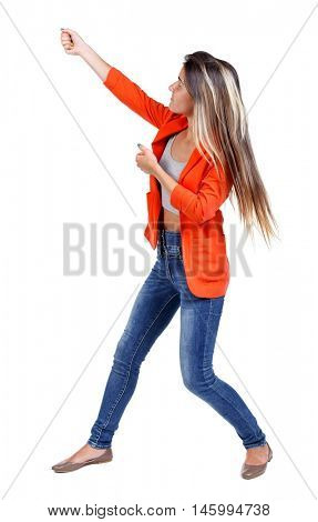 back view of standing girl pulling a rope from the top or cling to something. girl watching. girl in a red jacket, pulls a rope