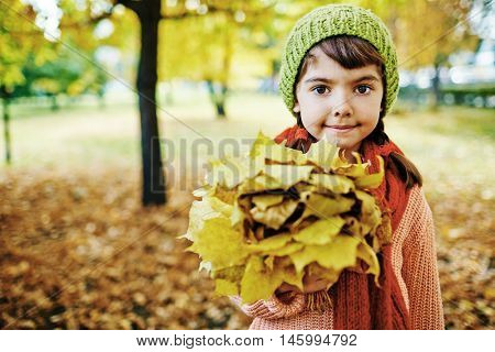 Portrait of cute little brunette girl with hazel eyes holding big bunch of golden maple leaves, smiling and looking at camera in park on perfect sunny autumn day