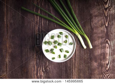 Sour creame. Round dish of homemade tartar sauce. Sour cream with green onion. sour cream and onion on a wooden dark background top view.