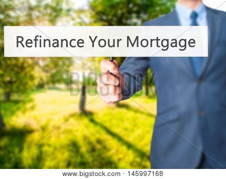 Refinance Your Mortgage - Businessman Hand Holding Sign