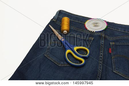 Trousers sewn from a blue denim and they are pins and thread scissors