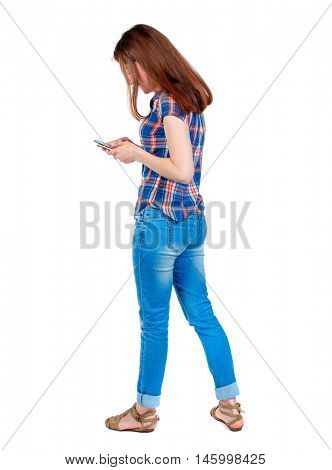 back view of standing young beautiful woman using a mobile phone or tablet computer. Girl in plaid shirt standing sideways inclining his head and looking at the phone.