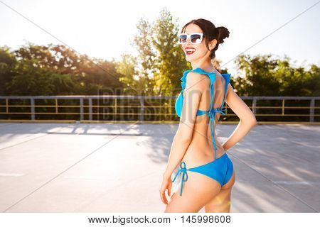 Side view of a beautiful young girl in blue swimsuit posing outdoors on the open road