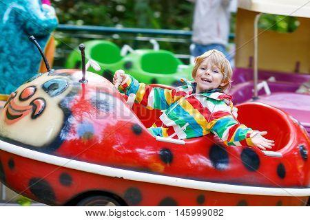Funny little kid boy riding on ladybug animal on roundabout carousel in amusement park. Happy preschool child having fun outdoors on sunny day.
