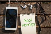 """Smartphone with blank area on touchscreen with in ear headset opened notebook with """"Good morning"""" written on pen smart phone and coffee cup on wood table in morning time pen and glasses on rustic wood table in morning time with natural lighting poster"""