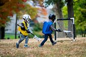 Active little kids playing lacrosse in forest camp poster