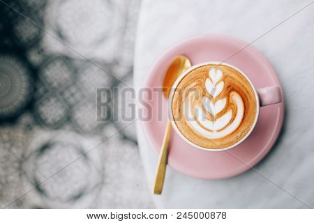 Two Beautiful Pink Cups Of Cappuccino With Latte Art On The Table.