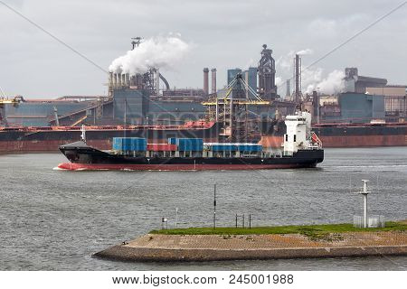 Big Steel Factory In Harbor Ijmuiden With Cargo Carriers And Container Ship In Front, The Netherland