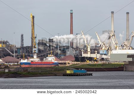 Big Steel Factory In Harbor Ijmuiden With Cargo Carrier In Front, The Netherlands