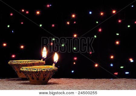 two  festive diyas or lamps .