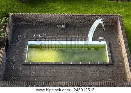Swimming Pool In A Garden With Green Water And A Slide Surrounded By A Brick Wall