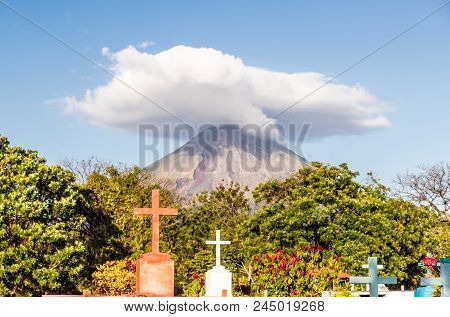 Ometepe, Nicaragua. February 2018. A view of the Volcano Concepcion with a religious icons in the foreground on ometepe island in Nicaragua. poster