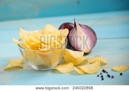 Crispy Potato Chips In A Glass Bowl With  Onions On Old Blue Wooden Background. Potato Chips Homemad