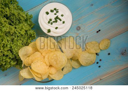 Crispy Potato Chips In A Glass Bowl With Sour Cream, Salad And Pepper On Old Blue Wooden Background.