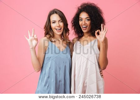Two beautiful summer girls 20s with different color of skin in dresses smiling at camera and showing ok or alright sign isolated over pink background