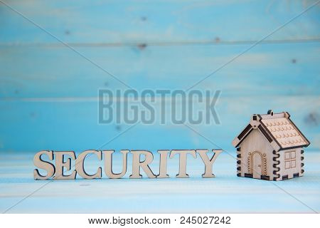 Small Model Of House With Word Security  On The Blue Background. Real Estate Concept. New House Conc