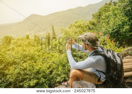 Man With A Beard Hiker In A T-shirt And Hat With A Backpack And An Action Camera Takes Pictures Of T