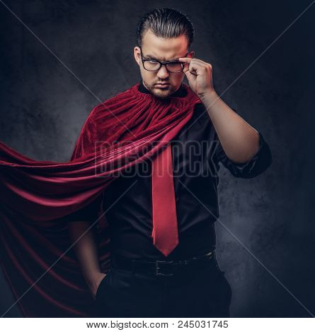 Portrait Of A Genius Villain Superhero In A Black Shirt With A Red Tie. Isolated On A Dark Backgroun