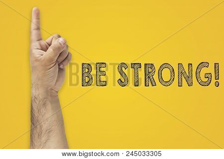 Be Strong, Success Concept. Hand Gesture Finger Pointing Finger Next To The Inscription: Be Strong.