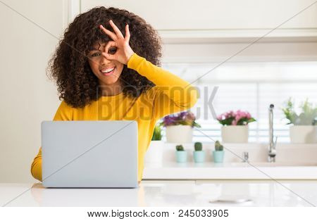 African american woman using computer laptop at kitchen with happy face smiling doing ok sign with hand on eye looking through fingers