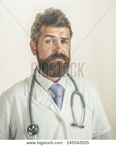 Portrait Male Doctor With Beard And Mustache Dressed In White Medical Robe. Physician With Stethosco
