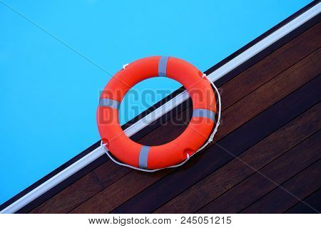 The Red Life Ring Lies On The Wooden Floor Of The Swimming Pool. Life Cycle, Floating Above The Sunn