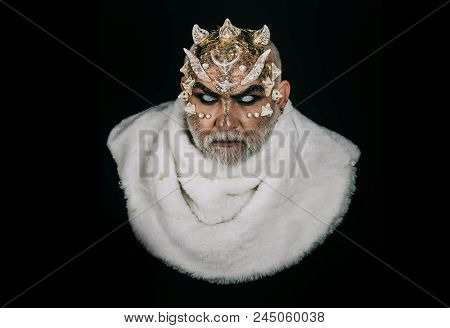 King With Reptilian Skin And Gray Beard Wearing White Fur. Man With Fictional Makeup On Black Backgr