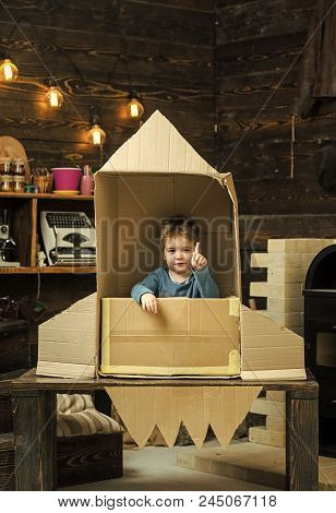Childhood Concept. Kid Sit In Cardboard Hand Made Rocket, Pointing Upwards. Boy Play At Home With Ro