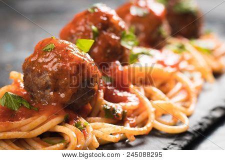 Meatballs served over italian spaghetti pasta with tomato sauce