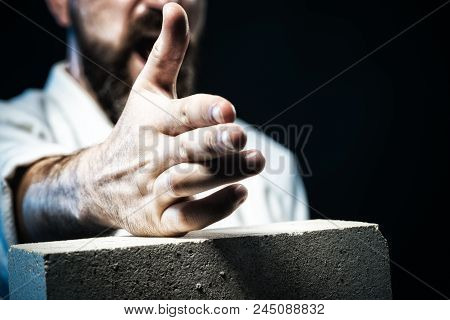 Karate Man Breaking With Hand Concrete Brick. Karate Fighter Showing Kick By Hand. Mma - Mixed Marti