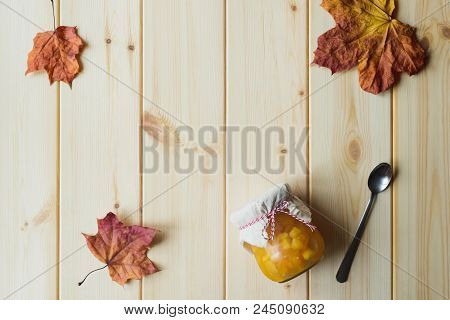 Top View Of Autumn Still Life Of Organic Pumpkin Jam In A Jar, Maple Leaves And Spoon On Natural Woo