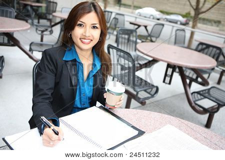 A pretty asian business woman at table with notebook