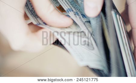Close-up Of A Businessman Hands Counting Dollar Bills In Wallet.