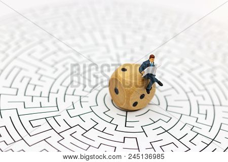 Miniature People: Businessman Reading On Center Of Maze. Concepts Of Finding A Solution, Problem Sol