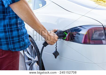 Man Inserts The Charger Into An Electric Vehicle. Electric Vehicle Charging Station For Home With Ev