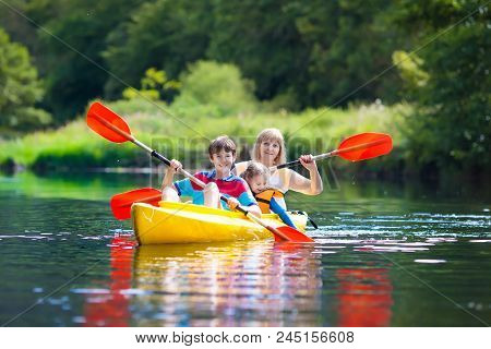Child With Paddle On Kayak. Summer Camp For Kids. Kayaking And Canoeing With Family. Children On Can