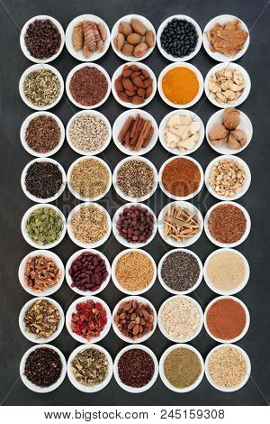 Healthy heart food ingredients with herbs and spices used in herbal medicine on slate background. Large collection high in vitamins, minerals, antioxidants, fibre and omega 3 fatty acids.