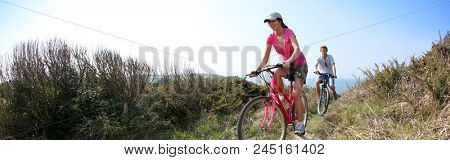Couple riding bike on country path, template