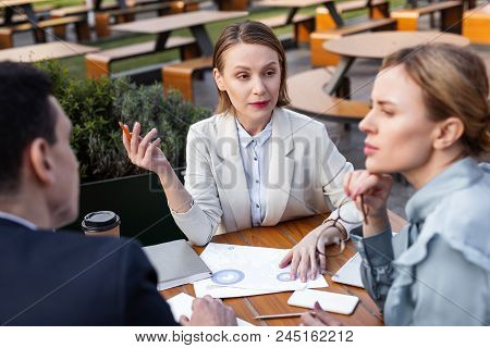 Beige jacket. Stylish experienced businesswoman wearing beige jacket feeling overloaded while attending staff meeting poster