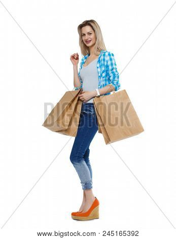 Front view of woman with shopping bags . beautiful brunette girl in motion.    Front view people collection. Isolated over white background.  Blonde in shoes with heels posing with paper bags