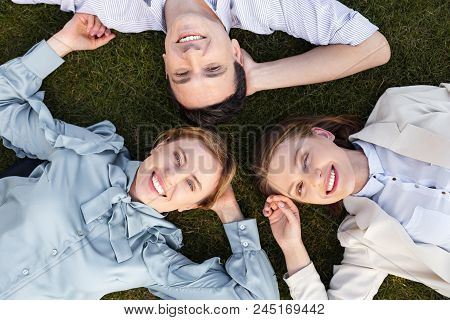Happy Employers. Three Smiling Happy Employers Feeling Relaxed While Lying On The Grass Outside The