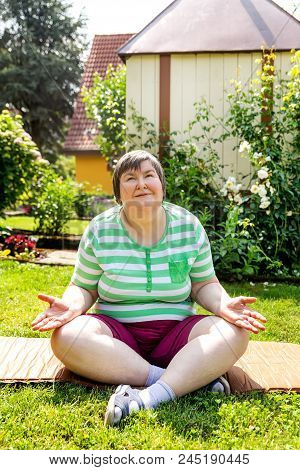 Single Mentally Disabled Woman Is Doing Some Relaxation Yoga Exercises In Her Garden At Home