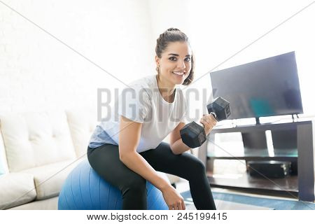 Portrait Of Cheerful Female Doing Arms Exercise With Dumbbells While Sitting On Stability Ball At Ho
