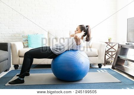 Side View Of Fit Young Latin Woman Doing Abs Exercise On Swiss Ball In Living Room
