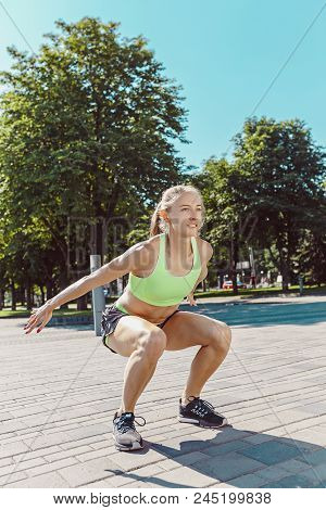 Fit Fitness Woman Doing Stretching Exercises Outdoors At Park. Girl Doing Hamstring Leg Stretching E