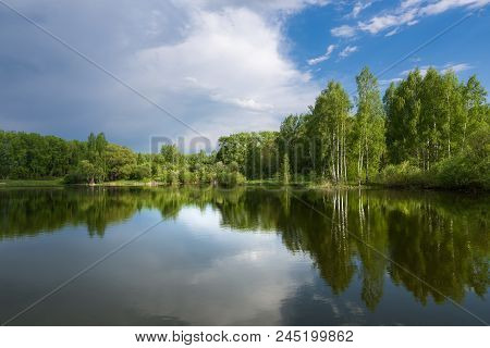 Trees That Grow On The Shore Of The Lake And The Cloudy Sky Are Reflected On The Surface Of The Wate
