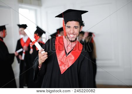 Happy student in bachelor robe with diploma indoors. Graduation day