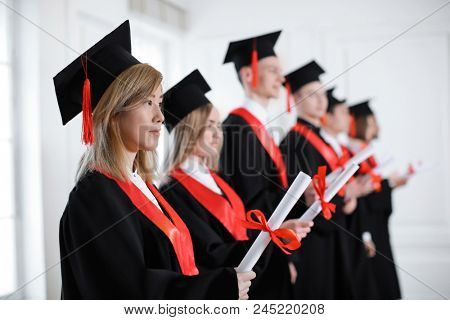 Students in bachelor robes with diplomas indoors. Graduation day